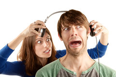 Woman interupts man with headphones Royalty Free Stock Images