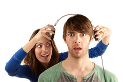 Woman interupts man with headphones Royalty Free Stock Image
