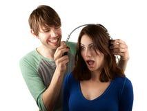 Woman interupts man with headphones Royalty Free Stock Photos
