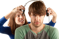 Woman interupts man with headphones Stock Images