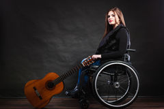 Woman invalid girl on wheelchair with guitar Royalty Free Stock Image