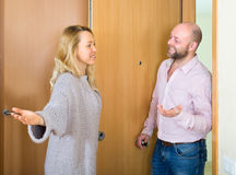 Woman invites male guest to come in Stock Photo