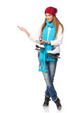 Woman inviting to skating-rink. Full length of smiling young woman carrying a pair of ice skates inviting you to skating-rink, over white background Royalty Free Stock Images