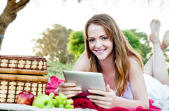 Woman with ipad tablet in park Royalty Free Stock Photography