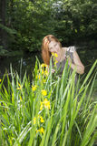 Woman among the irises in the water. The red-haired woman of average years stands among the irises in vodema and she smiles royalty free stock photography