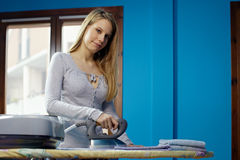 Woman with iron doing chores Royalty Free Stock Photo