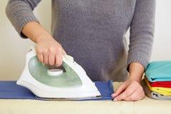 Woman ironing blue polo shirt Royalty Free Stock Photo