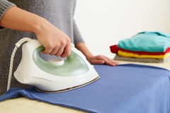 Woman ironing blue polo shirt Stock Photo