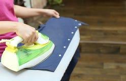 Woman ironing a blue shirt Stock Photos