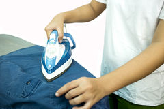 Woman ironing a blue shirt with a steam iron Royalty Free Stock Images