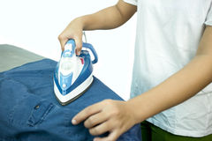 Woman ironing a blue shirt with a steam iron Royalty Free Stock Photo
