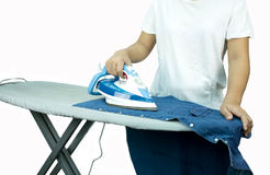 Woman ironing a blue shirt with a steam iron Stock Photography