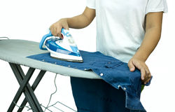 Woman ironing a blue shirt with a steam iron Stock Image