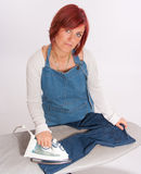 Woman ironing a childs jean Stock Photography