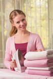 Woman ironing clothes. A beautiful young woman ironing her clothes royalty free stock photo