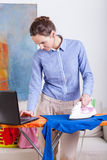 Woman ironing clothes and checking email on her laptop Stock Photos
