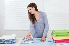 Woman ironing clothes in house Stock Photography