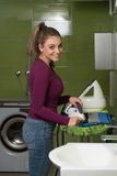 Woman Ironing Clothes In A Utility Room Stock Photos