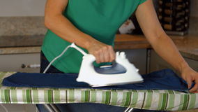 Woman ironing her clothing stock footage