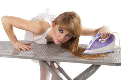 Woman ironing her hair Royalty Free Stock Photo