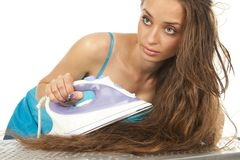 Woman ironing her hair Royalty Free Stock Photography