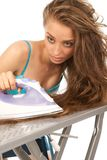 Woman ironing her hair Stock Photos