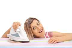 Woman ironing her hair with an iron Royalty Free Stock Photo