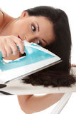 Woman ironing her hairs Stock Photography