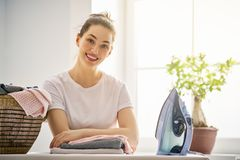 Woman is ironing at home. Beautiful young woman is smiling while ironing at home stock images