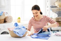 Woman is ironing at home. Beautiful young woman is smiling while ironing at home stock photo