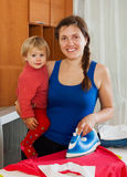 Woman ironing at ironing board in home Royalty Free Stock Images