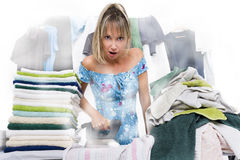 Woman ironing on ironing board many clothes Royalty Free Stock Photography