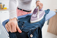 Woman Ironing Jeans Stock Photo