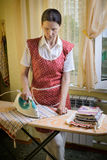Woman Ironing in the Kitchen Stock Photography
