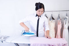 Woman ironing a pink shirt stock image