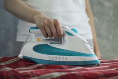 Woman Ironing a Red Checked Fabric. Closeup shot of a woman holding a steam iron Royalty Free Stock Photography