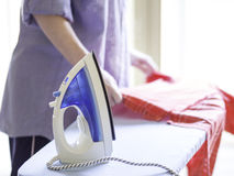 Ironing a red shirt Stock Photography