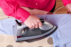 Woman ironing a shirt Royalty Free Stock Images