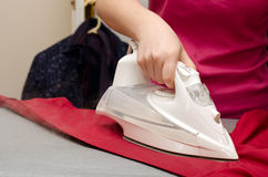 Woman ironing a shirt. A woman is seen ironing a shirt, with clothes in the background Stock Photos
