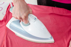 Woman ironing a tee shirt Royalty Free Stock Photos