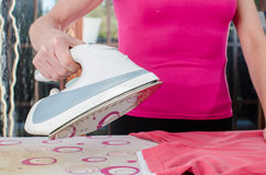 Woman ironing a tee shirt Stock Photo