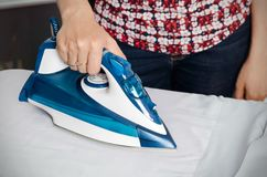 Woman irons clothes on ironing board with steaming iron Stock Photo