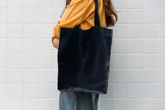 Free Woman Is Holding Black Bag Canvas Fabric For Mockup Blank Template Royalty Free Stock Images - 154203329