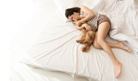 Free Woman Is Lying And Sleeping With Poodle Dog In Bed. Stock Images - 101383644