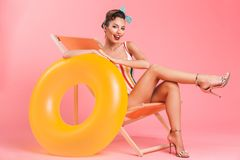 Woman isolated on beach chair with inflatable ring. Photo of young pin-up woman isolated over pink background wall in swimwear on beach chair with inflatable royalty free stock photography