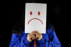 Depression. A woman in a blue sweater holding and covering and hiding her face with a white cardboard with a sad drawing sign rep. A woman isolated in black is royalty free stock photo