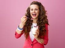Woman isolated on pink background eating farm organic yogurt Royalty Free Stock Image