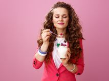 Woman isolated on pink background enjoying farm organic yogurt. Pink Mood. relaxed stylish woman with long wavy brunette hair isolated on pink background Royalty Free Stock Photos