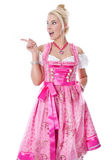 Woman isolated in a pink bavarian dirndl is pointing Stock Photos
