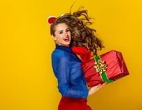 Woman isolated on yellow with red present box running Stock Photography